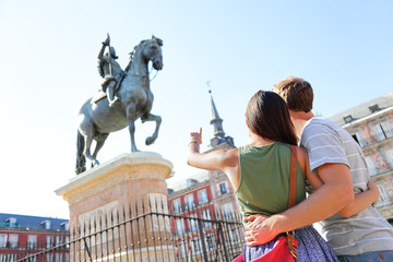 Madrid tourists on Plaza Mayor looking at statue