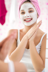 Happy young girl with  cosmetic facial mask