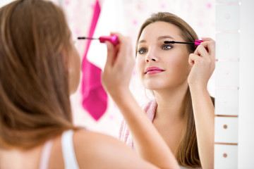 Makeup woman putting lipstick wearing hair rollers getting ready