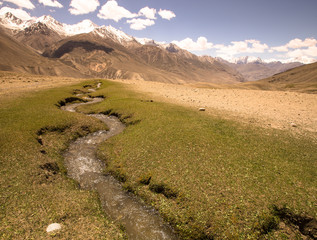 Tajikistan. Mountain stream flowing down from the barren peaks o