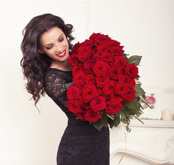 brunette woman in elegant dress, holding bouquet of roses