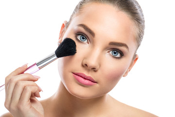 young woman with mirror applying powder on cheek