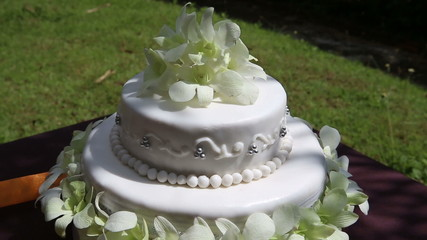 rotate fresh white orchid and beads decorated wedding cake