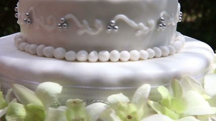 closeup fresh white orchid and beads decorated wedding cake