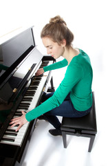 teenage girl plays piano in green shirt