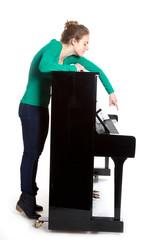 teenage girl plays piano in green shirt