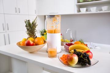 healthy smoothie ingredients in blender with fresh fruit