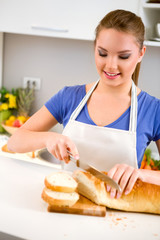 Young woman slicing fresh bread