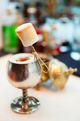 Cocktail with marshmallow in old metal goblet