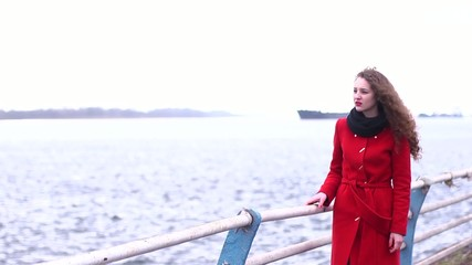 Beautiful girl in red coat on the promenade near the water