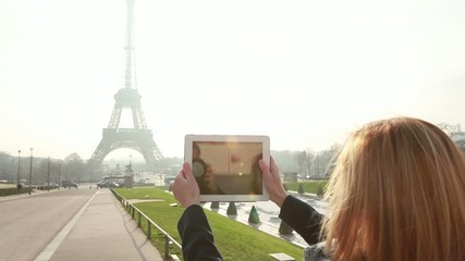 Tou g woman photographing Eiffel tower using digital tablet