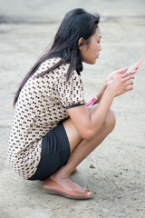Asian girl on the street with a cell phone