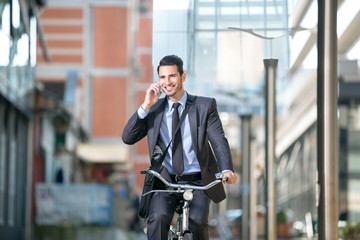 Businessman riding a bicycle and talking with mobile phone