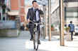 Young cheerful businessman riding a bicycle and using phone