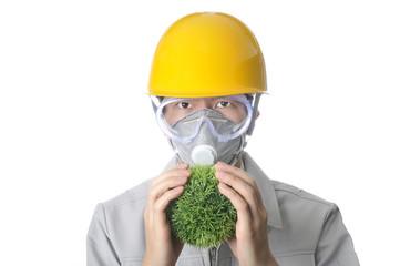 緑の球体を手にもってヘルメットをかぶっている男性