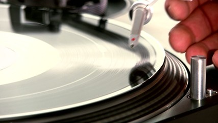 DJ Turntable. Dropping the needle on a spinning viny close-up