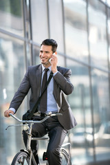 Young smiling business man with phone riding a bicycle
