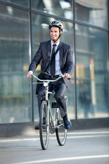 businessman riding bicycle by building