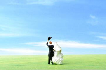 青空と草原をバックに歩く新郎新婦