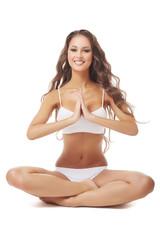 Smiling beautiful brunette posing in yoga pose