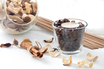 Aroma candle in the glass with coffee beans, cinnamon and perfum