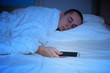 Man sleeping in bed and holding a mobile phone - 77294972