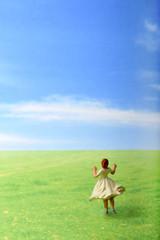 草原でダンスしているスカートを履いた女性のミニチュア人形