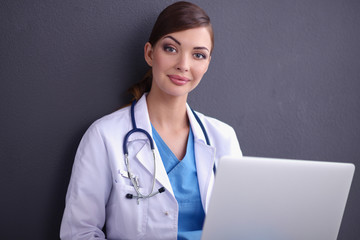 Female doctor working sitting on grey  background