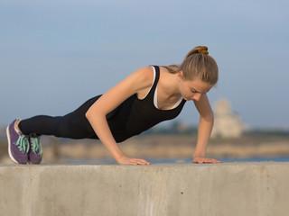 Girl doing exercises on open air