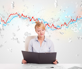Business woman sitting at table with stock market graph