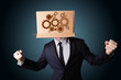 Businessman gesturing with a cardboard box on his head with spur