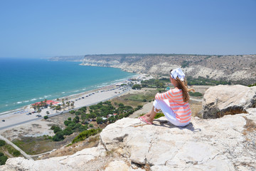 Girl on the rock looking to the ocean. Cyprus