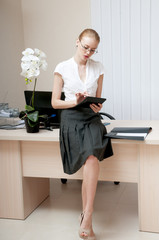 Young confident secretary busy in the office.
