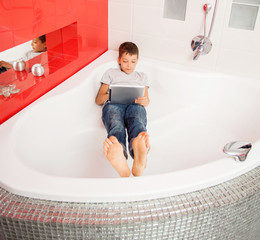 Boy hiding in the bathroom, playing in tablet