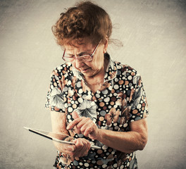 Old woman holding a tablet in the hands of