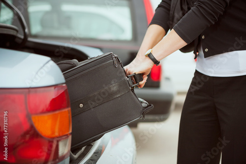Travel: Woman Pulling Suitcase Out Of Trunk
