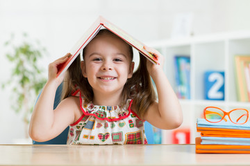 preschooler child girl with book over her head