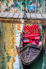 Luxury gondola under bridge on water canal in Venice, Italy