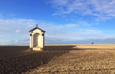 The small chapel on a empty autumn field