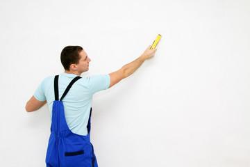 Young plasterer polishing a wall