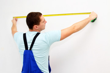 Young worker measure a wall
