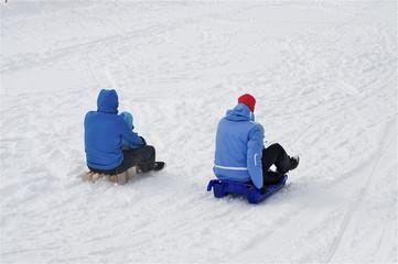 Familie am Schlitteln in blauen Schneeanzügen