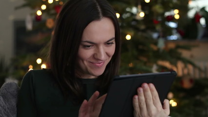 Woman with tablet computer. Christmas tree in background