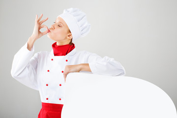 Smiling and cheerful female chef, cook or baker in uniform