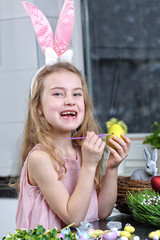 young girl in bunny ears painting Easter egg