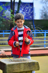 Boy playing wih a branch in the park