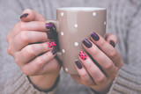 Fototapety Woman with manicured nails holding a cup
