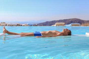 Young man in infinity swimming pool in Santorini, Greece