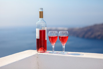 Two glasses and bottle of tasty red wine at sunset in Greece