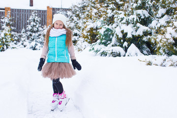 Adorable little girl skating in winter snow day outdoors